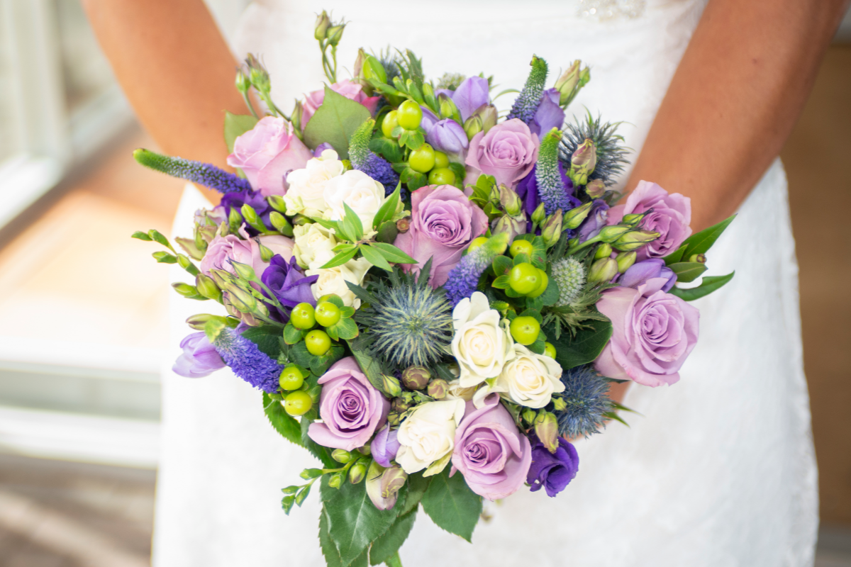 bride holding colourful lilac and green bouquet